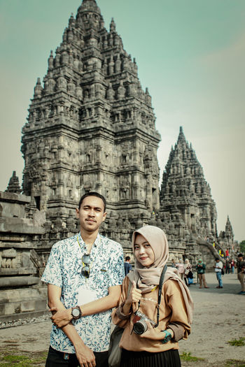 Portrait of couple standing against temple