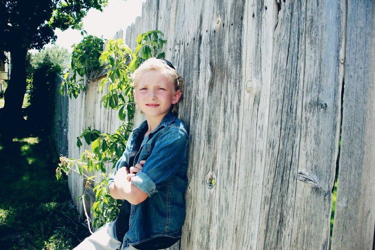 Portrait Of Sboy Leaning Against Fence