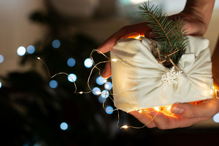 Cropped hands of person holding gift box with illuminated christmas lights