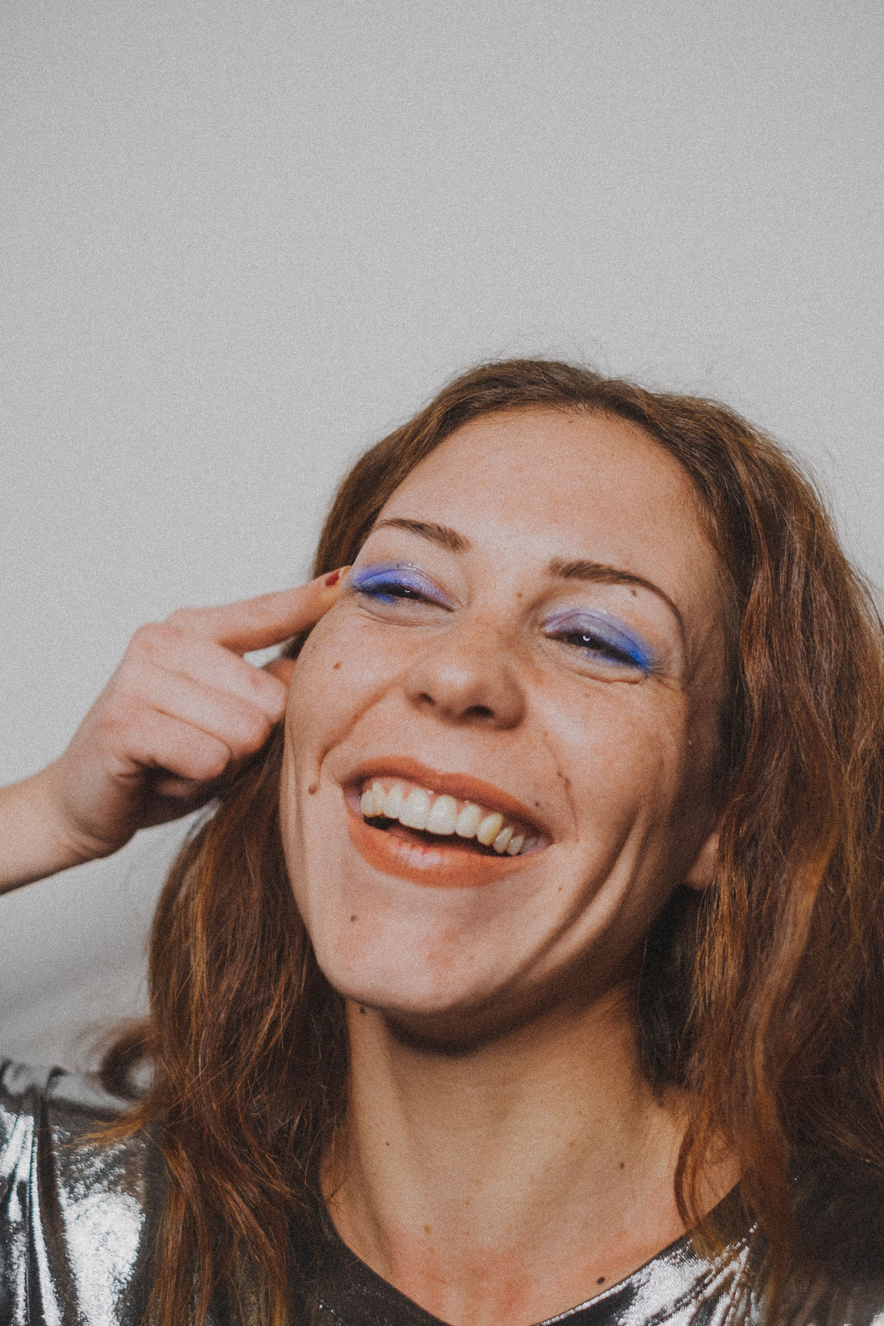 Smiling young woman with eye make-up against wall