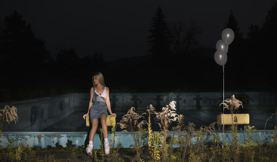 Young woman sitting on diving platform at swimming pool during night