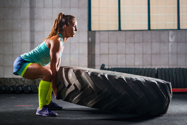 Mid adult woman carrying tire in gym