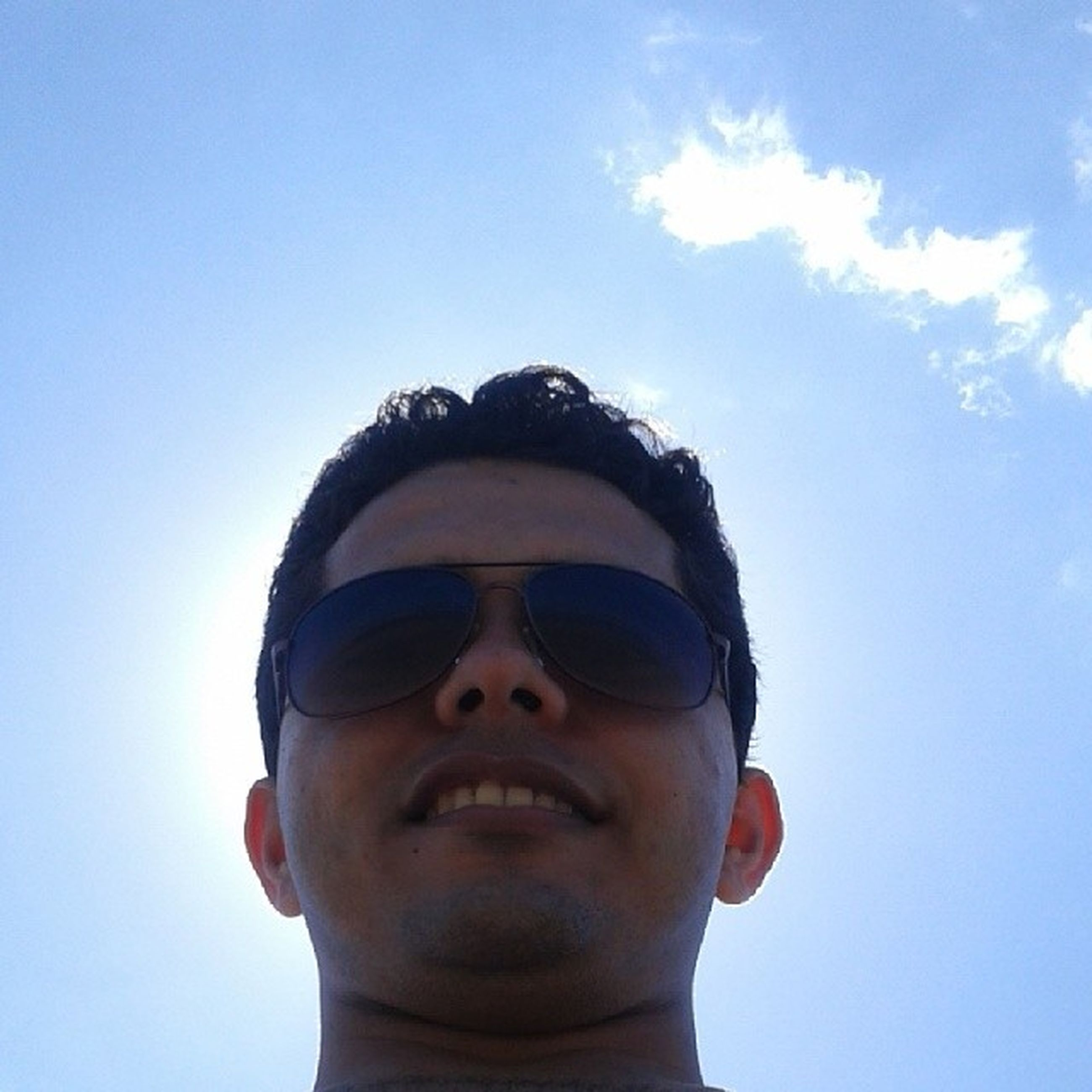 looking at camera, portrait, person, young adult, young men, front view, headshot, lifestyles, sunglasses, leisure activity, smiling, blue, mid adult men, low angle view, head and shoulders, mid adult, sky, happiness
