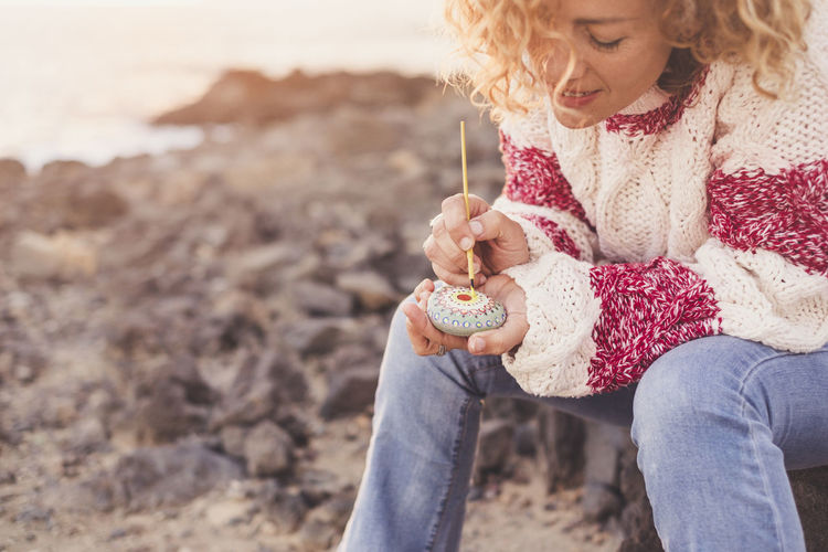 young woman curly hair sitting close the sea in relaxed moment vintage dressing Adult Beach Blond Hair Close-up Curly Hair Day Girls Human Hand Mandala Nature One Person Outdoors Painting People Playing Real People Relaxed Moments Sand Smiling Sunrise Sunset Vintage Dress