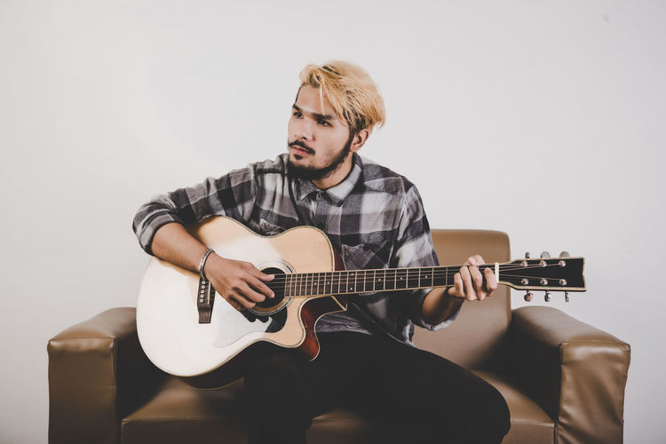 Young man playing guitar while sitting on armchair against white background