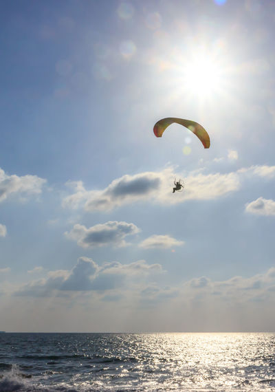 Parachute jumper on motorized parachute flying over the sea at sunset Coastline Parachute Jumper Sportsman Adventure Beauty In Nature Day Extreme Sports Flying Horizon Over Water Leisure Activity Lifestyles Motorized Parachute Nature One Person Parachute People Real People Scenics Sea Sky Sport Sun Sundown Sunset Water