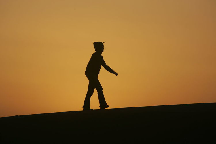 Walking on desert dune on the outskirts of Dubai Beauty In Nature Desert Leisure Activity Nature Outdoors Silhouette Sky Sunset Tranquility