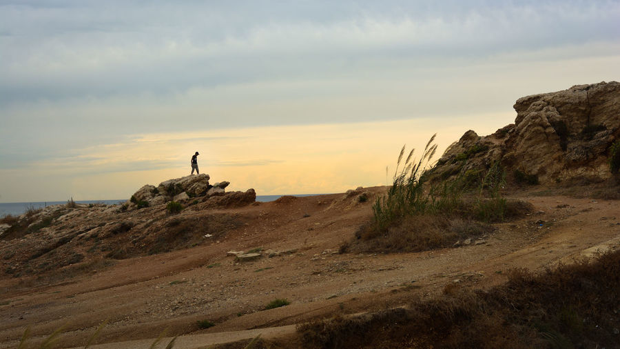 Mid distance of man standing on rock against sea during sunset