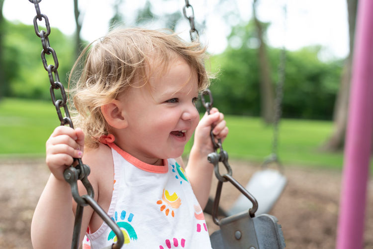 Close-up of girl on swing at playground