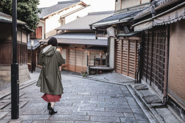 Rear View Of Woman Wearing Raincoat Walking On Street Amidst Buildings