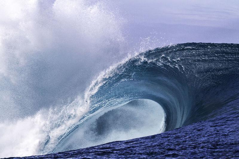 Sea waves rushing towards shore against sky