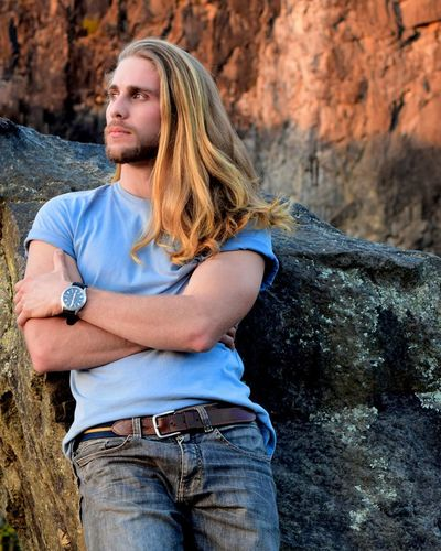 Man With Long Hair Standing Against Rock