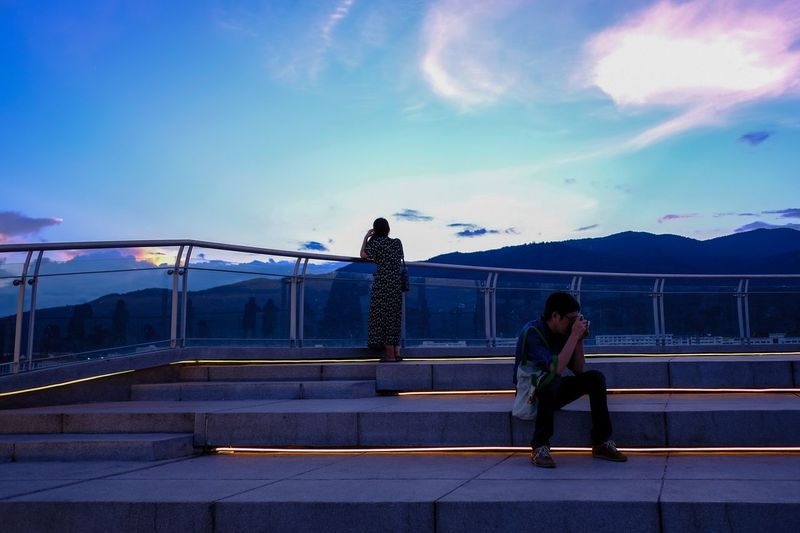 Man photographing while woman standing by railing against sky