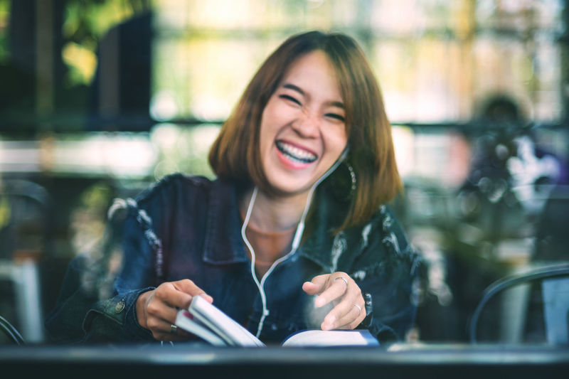 Portrait of cheerful young woman seen through glass sitting in cafe