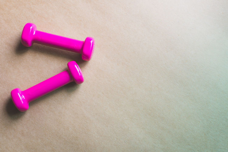 Fitness Equipment Dumbbell Indoors  Pink Color Close-up Still Life No People Table Weight Weights Two Objects Copy Space Exercise Equipment High Angle View Weight Training  Wood - Material Sports Training Sports Equipment Studio Shot