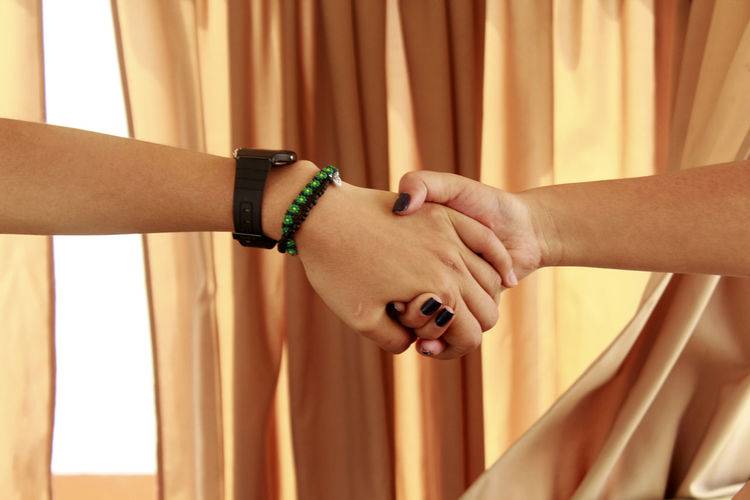 Close-up of couple holding hands against curtain