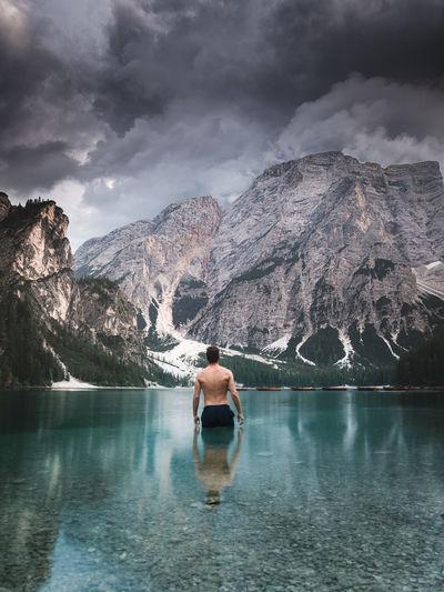 Rear view of shirtless man in swimming pool against lake