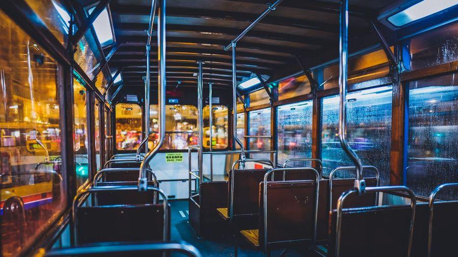 Empty seats in illuminated tramp at night