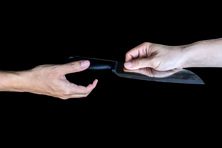 Close-up of hand holding paper over black background
