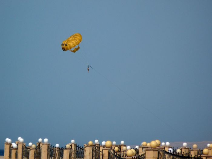 Low Angle View Of Person Parachuting In Blue Sky At Dusk