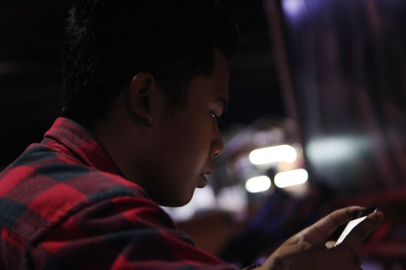 Side view of man using phone