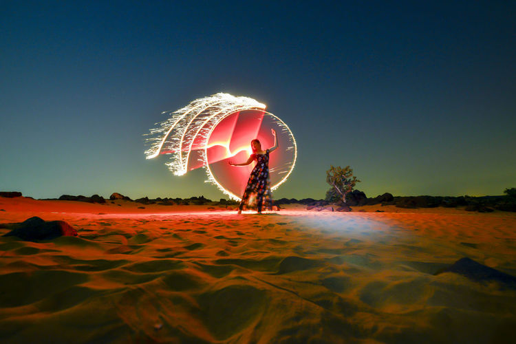 Full length of woman standig on sand against wire wool and sky