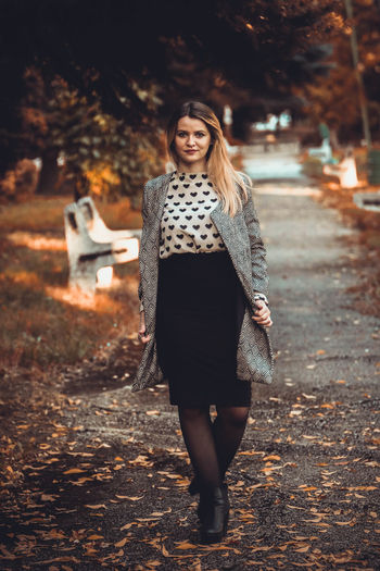 Portrait Of Smiling Young Woman Standing At Public Park During Autumn