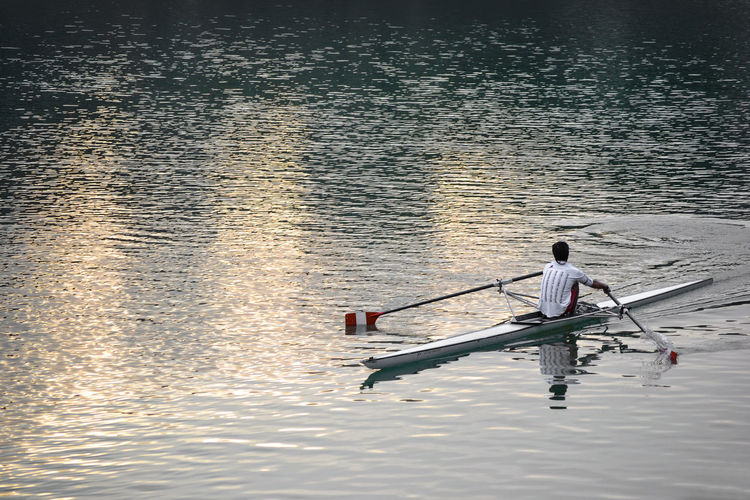 Rear View Of Man Canoeing On River