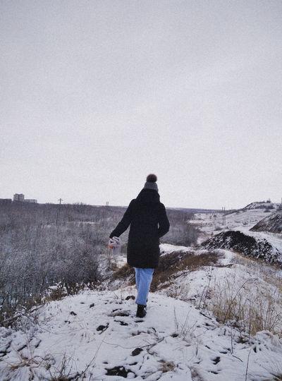 Rear view of man on snowy field against sky