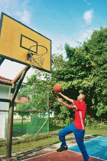 Man playing with basketball hoop against sky