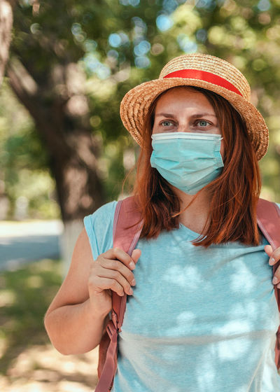 Caucasian tourist girl in summer straw hat with  backpack and  protective mask. travel and vacation