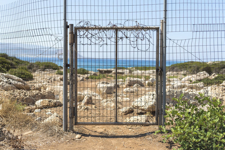 A fence in Greece Architecture Barrier Boundary Built Structure Day Fence Field Gate Land Landscape Metal Nature No People Outdoors Plant Protection Safety Security Sky Sunlight