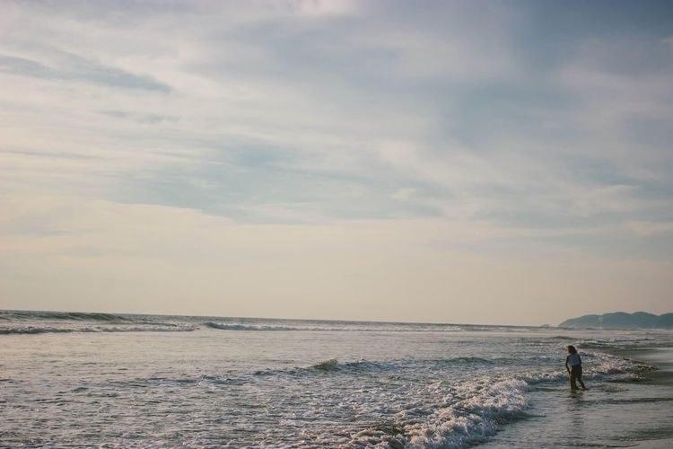 A man passes by the beach. Adult Adults Only Beach Beauty In Nature Cloud - Sky Day Daylight Holiday Horizon Horizon Over Water Horizontal Nature Occupation One Person Only Men Outdoors People Sand Sea Sky Sunset Travel Vacation Water Waves