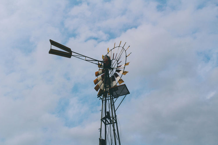 Low angle view of water wheel against cloudy sky