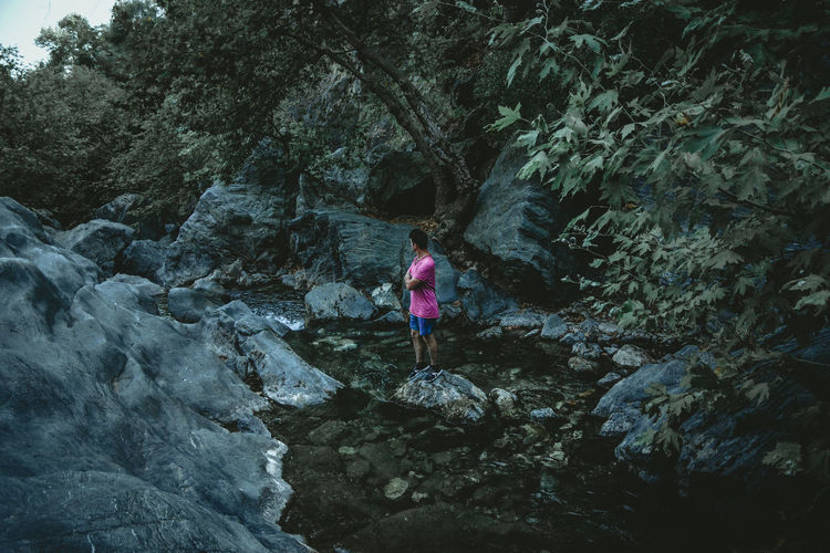 Full length of man standing on rock by water in forest