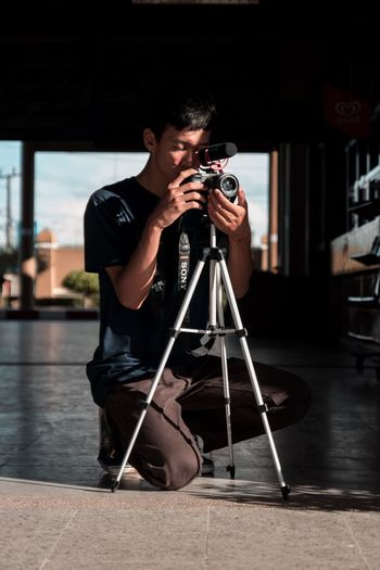 Filmaker Filmaker One Person Holding Real People Photography Themes Men Full Length Tripod Technology Occupation Camera - Photographic Equipment Artist Photographer Arts Culture And Entertainment Photographing Front View