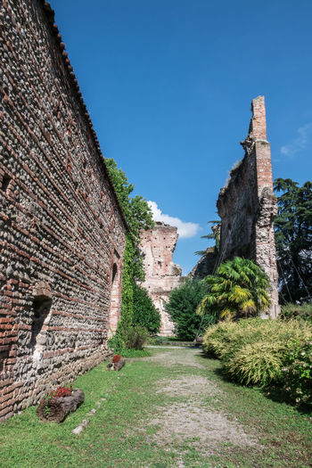 Outdoor gardens of Visconteo Castle. Trezzo sull'Adda (MILAN), ITALY. Adda Ancient Antique Architecture Castle Dadda Devil Exterior Lombardy Nature Background Blue Building Europe Garden Hill Historic House Italy Landscape Medieval Old Outdoor River Sky