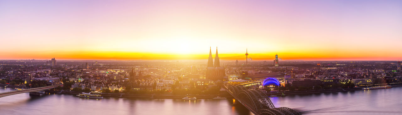 Hohenzollern bridge and cologne cathedral in city during sunset