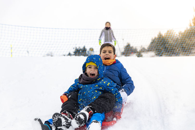 Family with a sled Sled Sledding Cold Temperature Snow Winter Two People Childhood Men Togetherness Males  Child Leisure Activity Boys Emotion Warm Clothing Family Enjoyment Real People Father Playing Son Positive Emotion Tobogganing