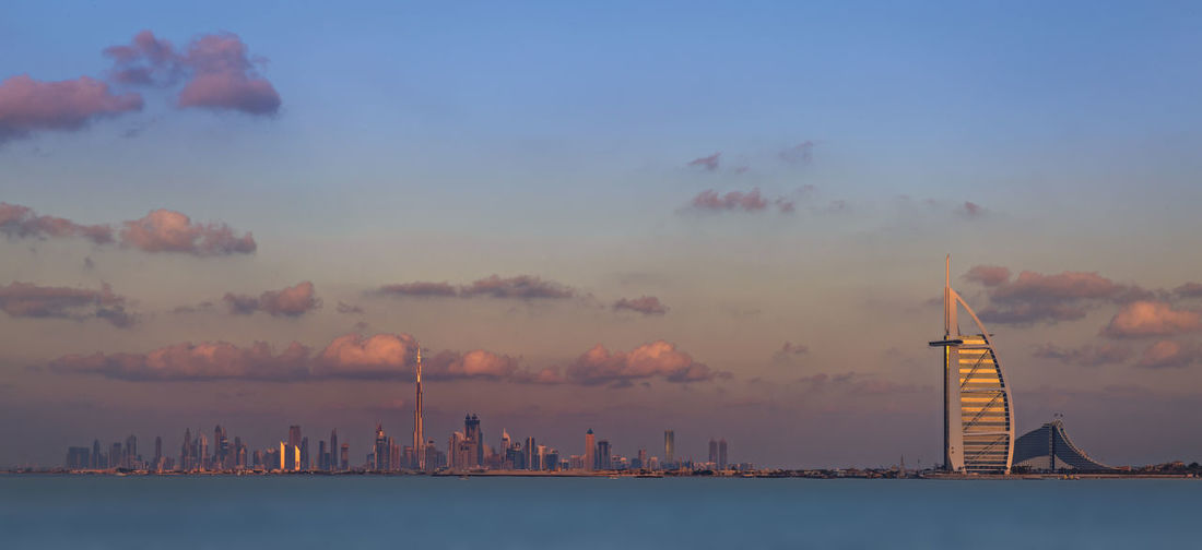 Burj Al Arab Hotel In Front Of River Against Sky At Dusk In City