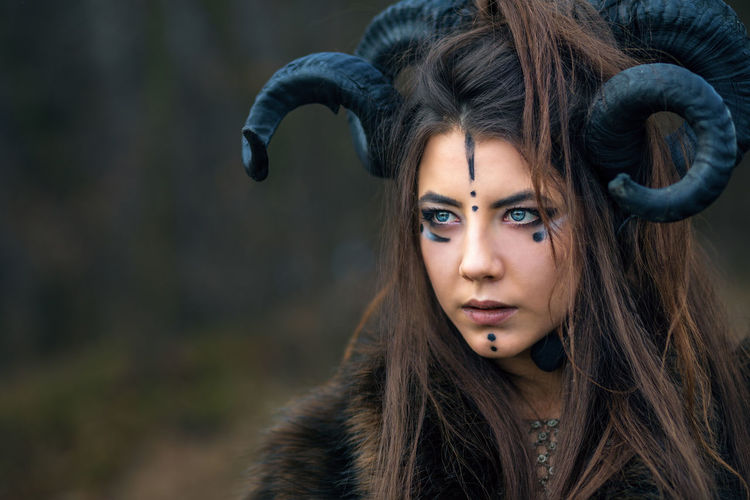 Close-up of serious woman with painted face wearing horns