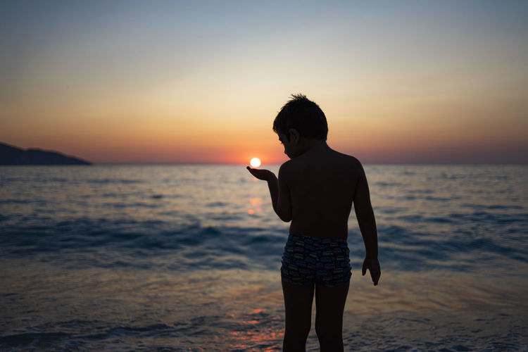 Little kid playing with the sun on the beach at sunset