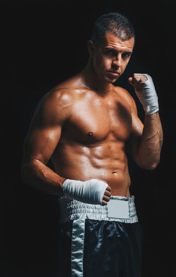 Portrait of shirtless male athlete wearing hand wrap while standing against black background