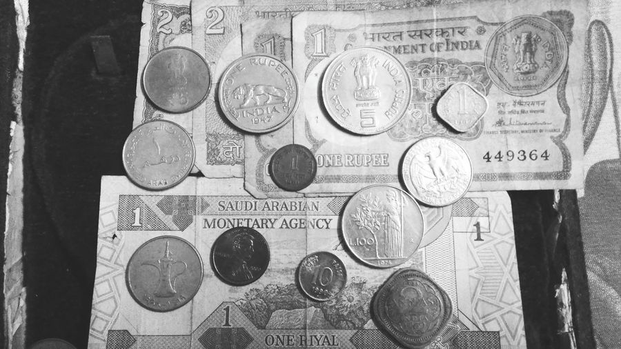 Close-up of coins on table against wall
