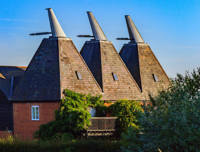 Oast House , Garden of England, Kent, England. Built Structure Architecture Nature No People Sky Outdoors Hops Beer Travel Destinations Tourism Getty Images Vivid International Shepherd Neame Iconic Buildings Village Rural Scene Countryside Landscape Building Exterior Building Plant Day Blue Low Angle View Tree Residential District Sunlight House Alternative Energy Renewable Energy Roof Environmental Conservation Farm Architecture