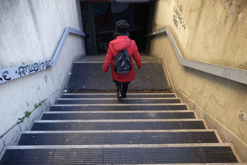 Entrance Underpass Architecture Built Structure Casual Clothing Concept Dangerous Day Full Length Leisure Activity Lifestyles One Person Outdoors Real People Rear View Staircase Standing Steps Steps And Staircases Walking Warm Clothing Women