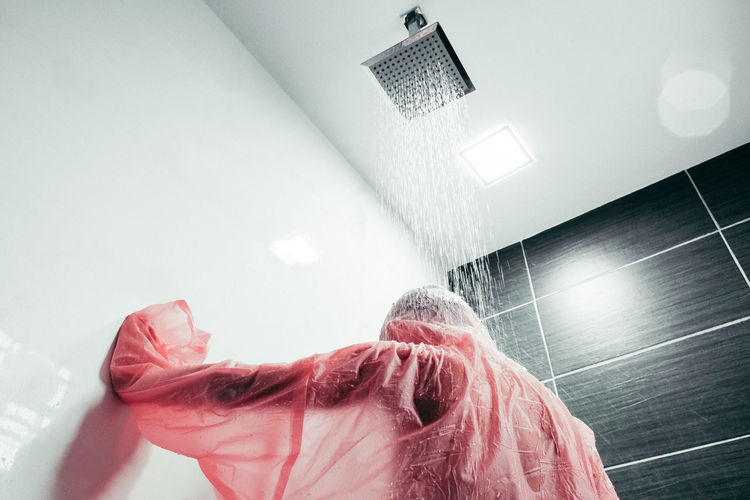 Low angle view of man in raincoat taking shower