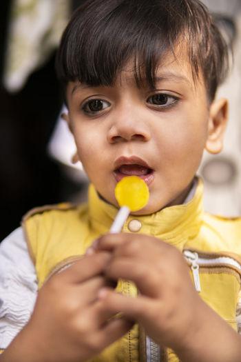Portrait of cute boy holding yellow camera