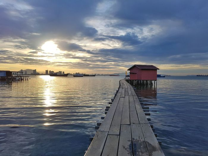 Morning view at Tan Jetty located along Weld Quay, George Town, Penang, Malaysia. Water Sea Nautical Vessel Sunset Harbor Beach Wood - Material Red Jetty Blue Boardwalk Seascape Horizon Over Water Romantic Sky Coastal Feature Low Tide Dramatic Sky Coast
