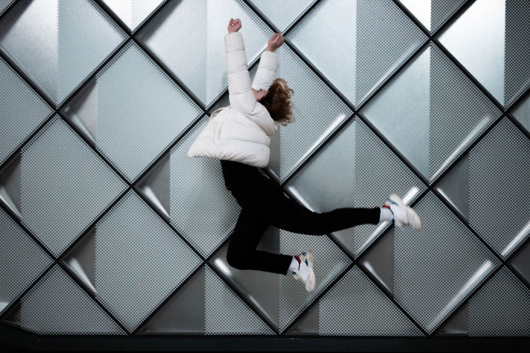 Side view of young woman in mid-air jumping against pattern wall